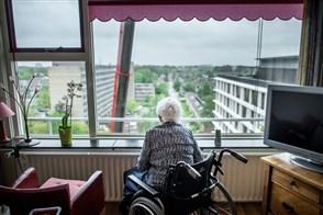 Oudere dame in rolstoel kijkt naar buiten