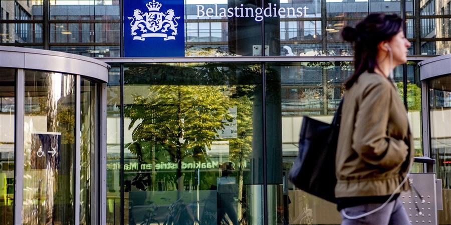 Vrouw loopt langs ingang gebouw belastingdienst