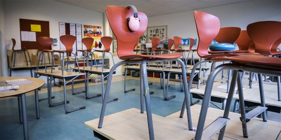 Een leeg klaslokaal met de stoelen op de banken