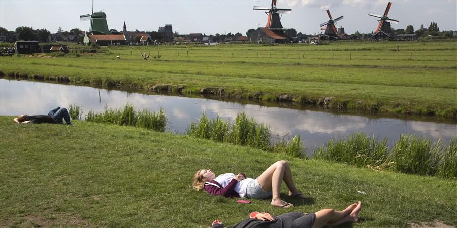 Toeristen luieren en relaxen en ontpannen en chillen in de zon, liggend in het gras met op de achtergrond de beroemde molens.