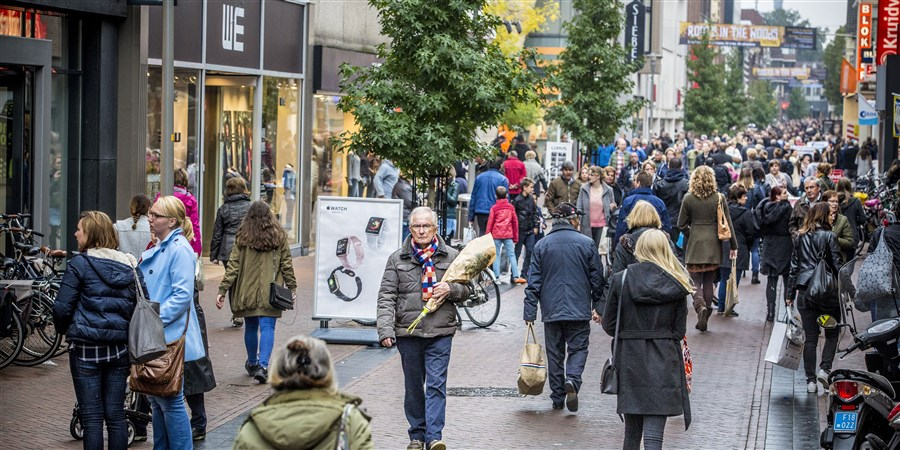 Winkelend publiek, man met een bos bloemen in een winkelstraat in Apeldoorn