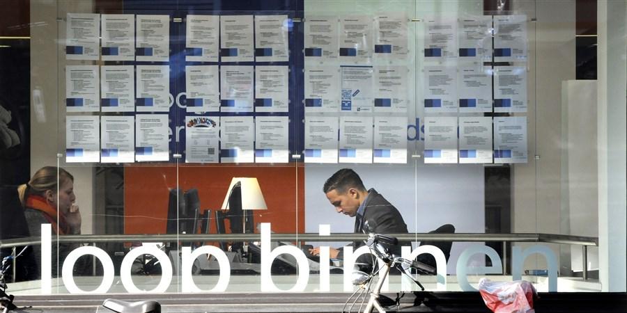 Etalage van een uitzendbureau, waar twee medewerkers aan het werk zijn