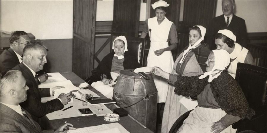 Historisch beeld. Bejaarden en hun verpleegster brengen hun stem uit in een stemlokaal tijdens gemeenteraadsverkiezingen van 1939
