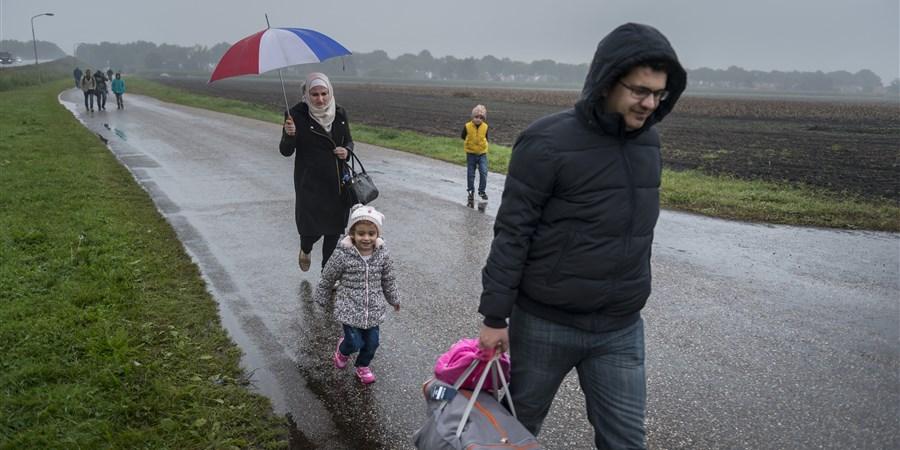 Asielzoekers lopen  over de weg Ter Apelervenen van en naar het azc