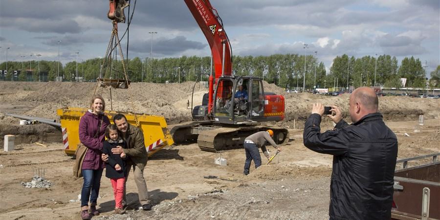 Man fotografeert gezin op de plek waar hun toekomstig huis wordt gebouwd
