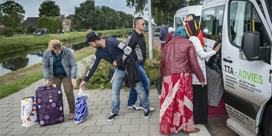 Vluchtelingen stappen een busje