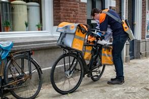 Bezorger van PostNL bij zijn fiets