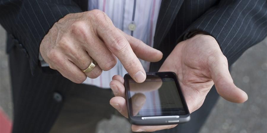 Man tikt iets op smartphone. Je ziet alleen zijn telefoon en hand.