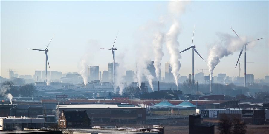Aanzicht van windturbines en rokende schoorstenen van bedrijven