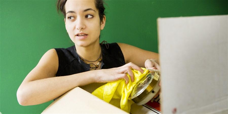 Meisje maakt doosje schoon wat ze uit verhuisdoos heeft gehaald