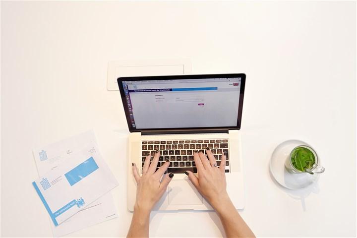 Handen aan laptop van bovenaf gezien