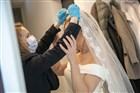 Bruid krijgt sluier omgeslagen door vrouw die zichzelf beschermt met handschoenen en een mondkapje.