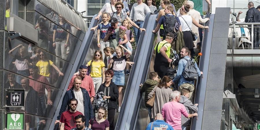 Drukte winkelend publiek in centrum Rotterdam. Topdrukte koopgoot. Via de roltrap gaan ze winkelstraat in en uit.