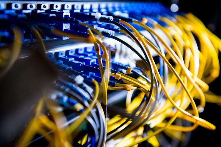 Blauwe en gele draden in patchkast van computernetwerk