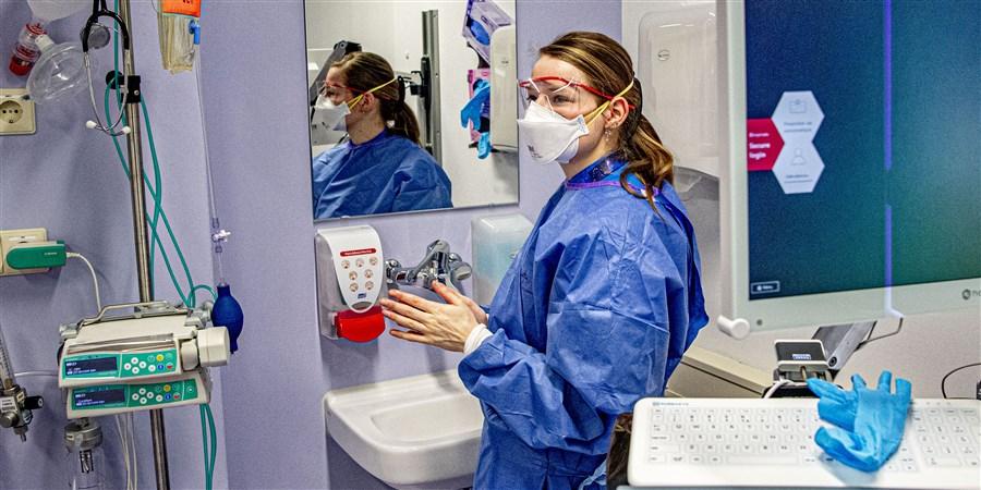 Verpleegkundige met mondkapje en gezichtsbescherming voor de spiegel in de quarantainekamer van een ziekenhuis