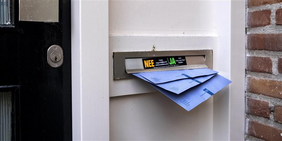 De blauwe envelop van de belastingdienst steekt uit brievenbus