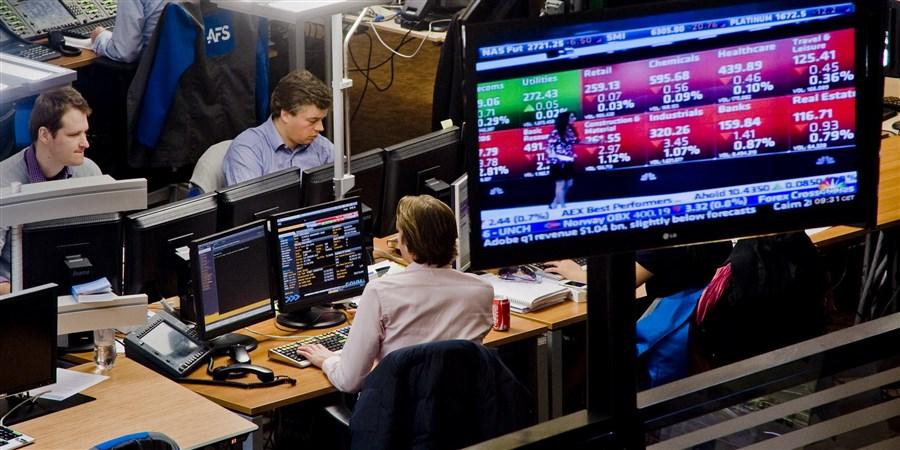 Beurshandelaren aan het werk achter hun computerschermen