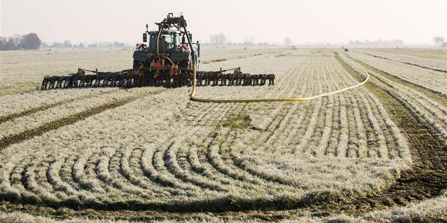 Boer rijdt mest uit.