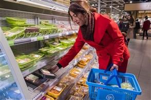 Een vrouw koopt groente, vlees en kaas bij de supermarkt