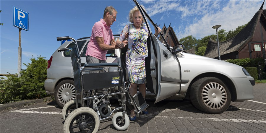 Man helpt minder valide vrouw vanuit auto naar rolstoel