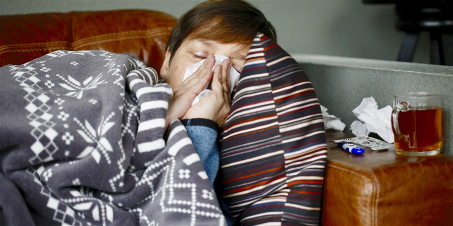 Een vrouw ligt onder een dekentje op de bank en snuit haar neus
