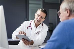 Dokter laat iets zien op tablet aan een patiënt, een oudere man met een bril en een blauwe trui