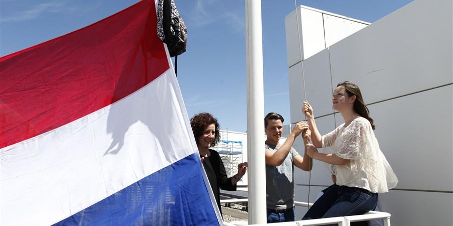 Meisjes en jongen hangen vlag met tas op.