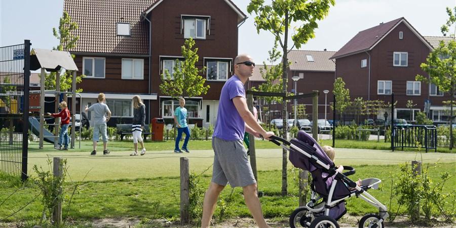 Man maakt een wandeling met zijn kind in kinderwagen in vinexwijk