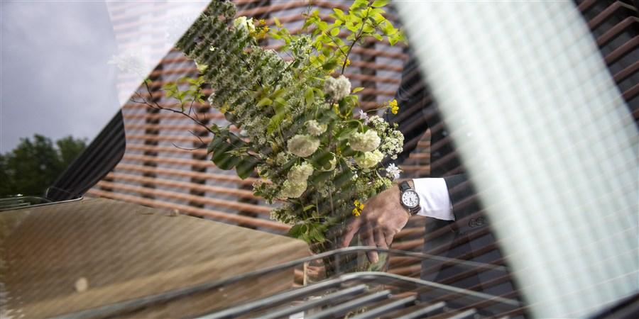 Iemand legt bloemen in een lijkwagen