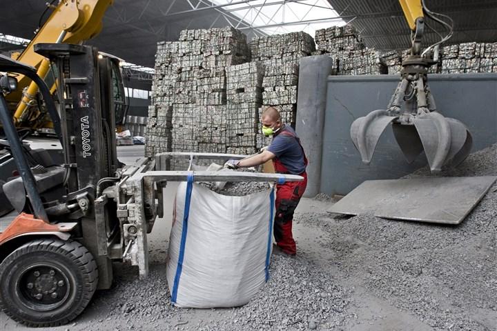 Metaalverwerking, werknemer schept grondstof in zak voor verdere verwerking
