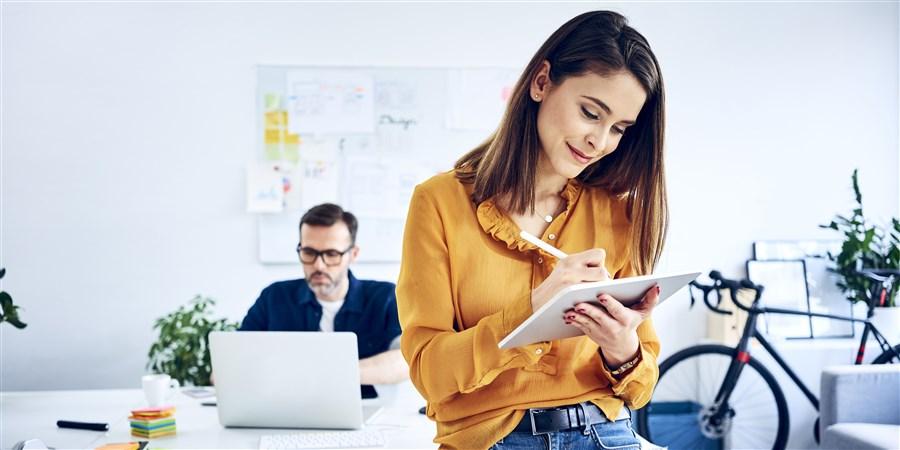 Zakenvrouw gebruikt tablet op kantoor met collega op de achtergrond