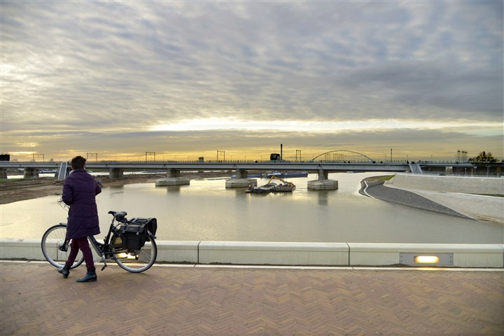 Woman walks over a bridge with her bicycle, looking at the railway bridge over the river Waal