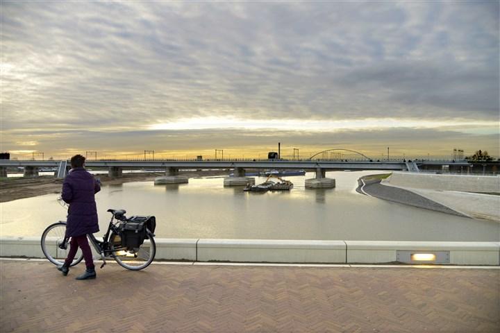 Vrouw loopt met fiets aan de hand over brug, kijkend naar spoorwegbrug over de Waal