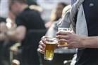 Mensen drinken een drankje op Stadhuisplein, drukke dag op de terrassen door het mooie voorjaarsweer en de marathon. Jonge man drinkt veel, 2 biertjes tegelijk. Voltanken, drink met mate, overmatig gebruik.