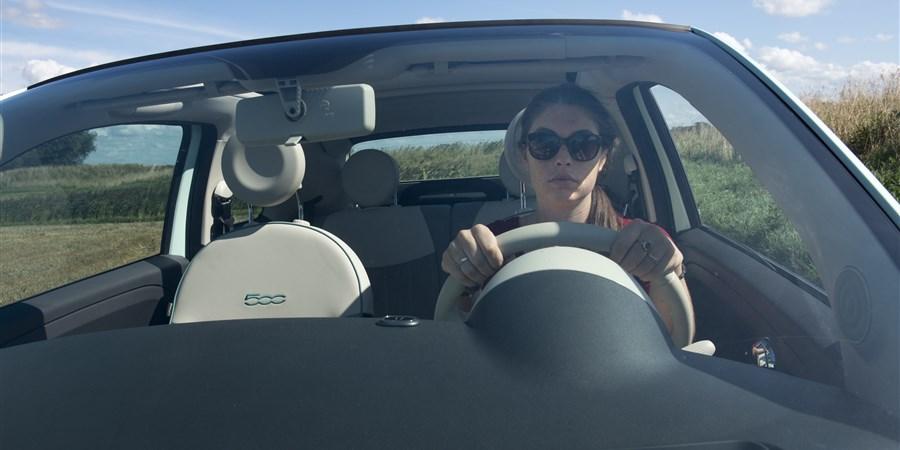 Jonge meid in de zomer op het platteland, Ze rijdt in een fiat, met open dak