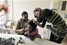 Huisarts onderzoekt oren van kind dat bij moeder op schoot zit