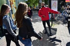 Een verkeersregelaar wijst twee vrouwelijke voorbijgangers in de stad in welke richting ze moeten lopen