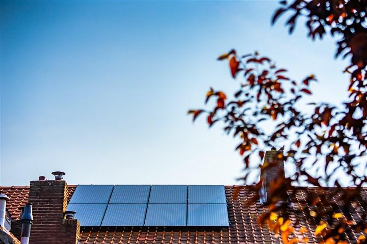 Zonnepanelen op een dak met een blauwe lucht