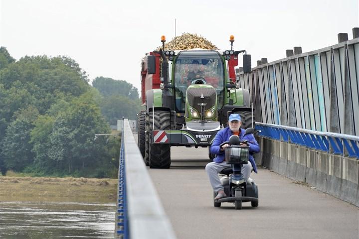 Uien zijn geoogst en een trekker rijdt over de brug over de rivier de maas naar de schuur waar de opslag plaatsvindt. een man in een scootmobiel rijdt langzaam voor hem uit