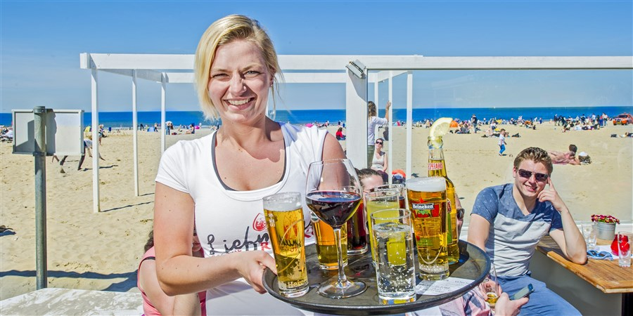 Serveerster bij strandtent met blad vol drinken