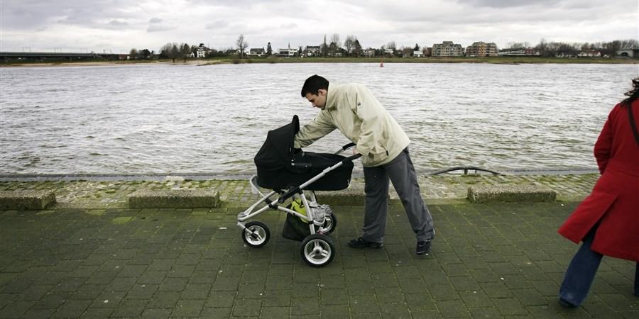Vader loopt met kinderwagen over waaklade