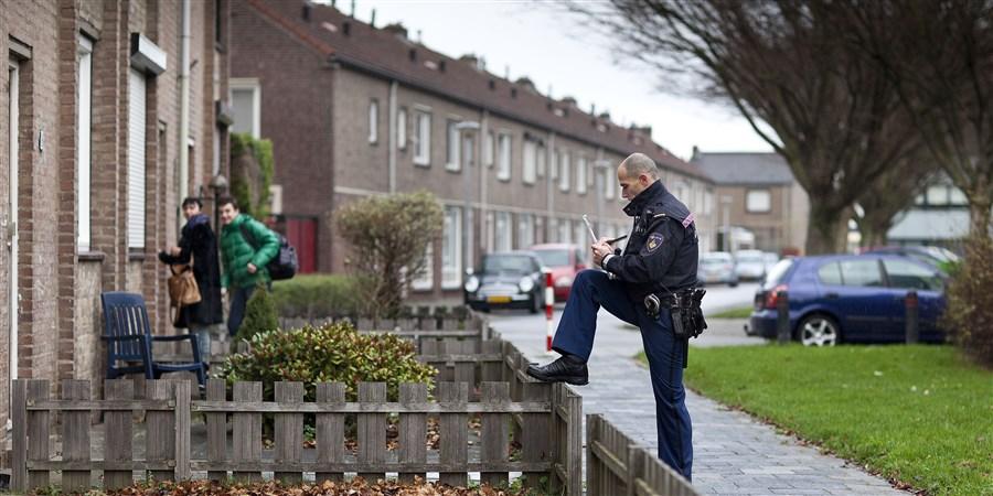 Een politieagent houdt een wijkschouw om bewoners attent te maken op inbraakgevoelige huizen.