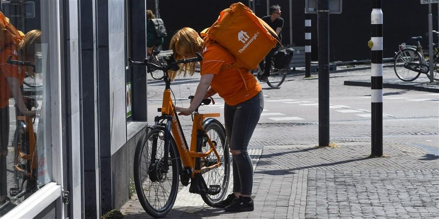 Een maatlijdbezorgster bij haar fiets