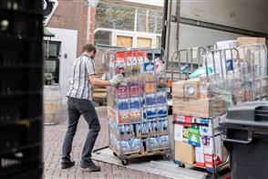 Een man laadt levensmiddelen uit een vrachtwagen