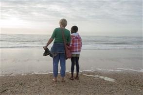 Moeder met haar geadopteerde dochter op het strand