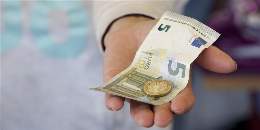 Hand waarin geld ligt. Briefje van 5 euro en een munt 1 euro