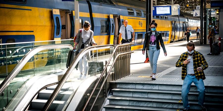 Reizigers met mondkapjes op het Centraal Station van Eindhoven