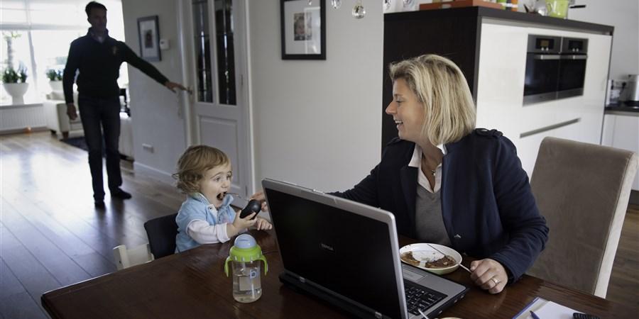 Jongetje krijgt eten van moeder die achter laptop zit.