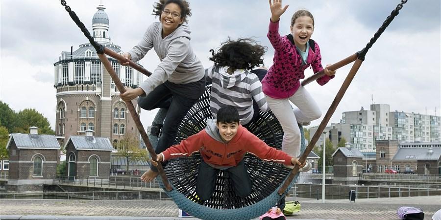 Allochtone en autochtone kinderen hebben samen lol met het schommelen in wijk Kralinger Esch