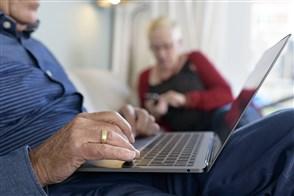Foto man achter laptop